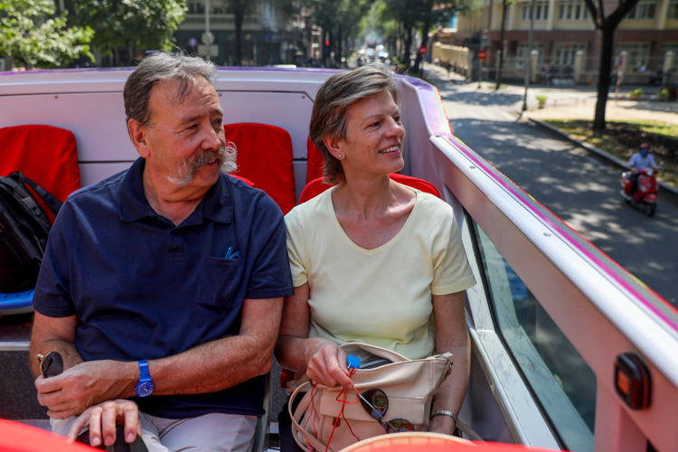 Du khách nước ngoài ngắm đường phố Sài Gòn từ xe buýt mui trần. Ảnh: Quỳnh Trần.