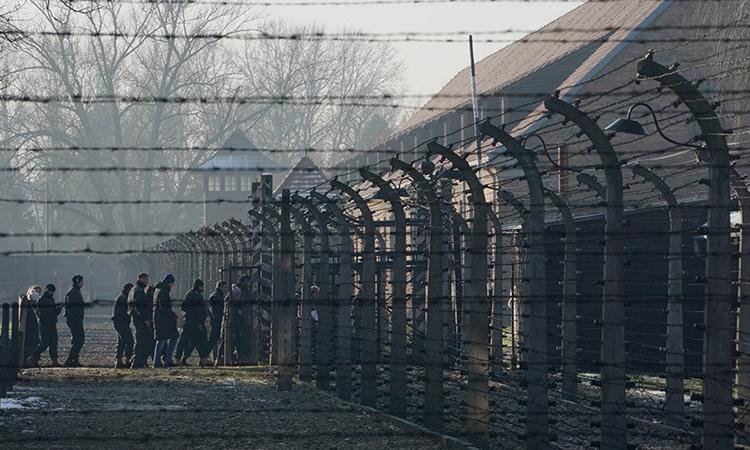Du khách đi qua hàng rào dây thép gai vào thăm trại Auschwitz ở Đức tháng 12/2019. Ảnh: AFP.