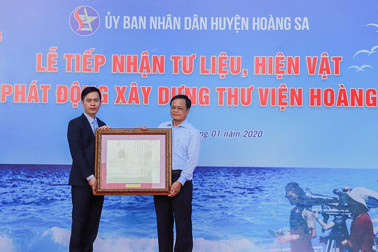 Ông Đặng Thanh Tùng (bìa trái) tặng châu bản triều Nguyễn cho Chủ tịch UBND huyện Hoàng Sa. Ảnh: Nguyễn Đông.