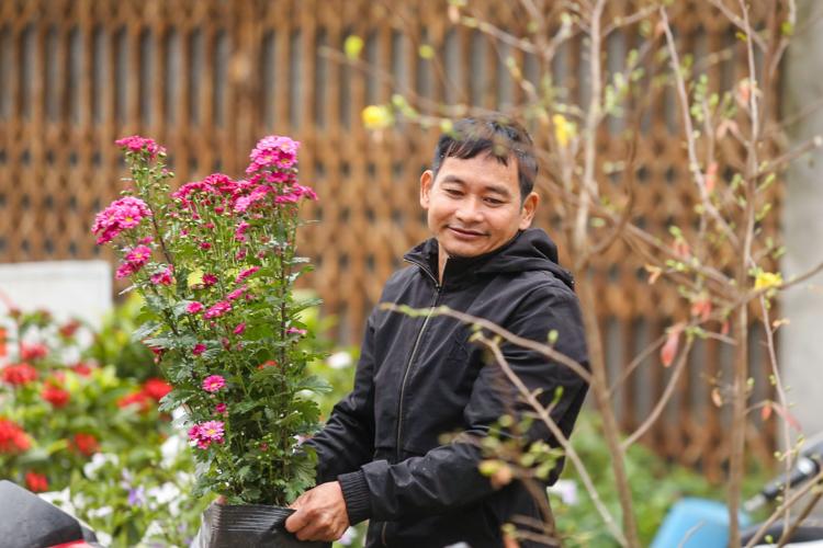 Anh Nguyễn Văn Sự mang hoa ra trung tâm xã để bán. Ảnh: Phong Vân.