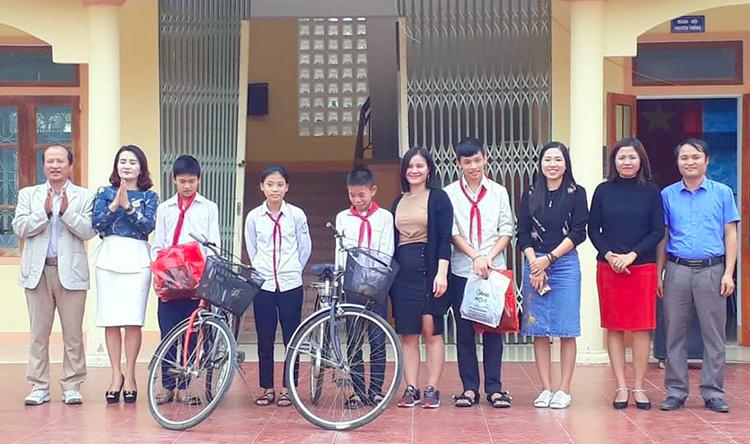 Cô An (thứ 5 từ phải qua) cùng các thành viên nhóm Khăn Hồng tặng xe đạp cho học sinh ở Hà Tĩnh. Ảnh: NVCC