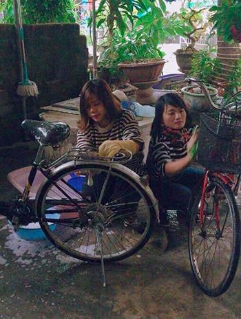 Cô Thỏa (bên phải) cùng đồng nghiệp lau chùi xe đạp. Ảnh: NVCC