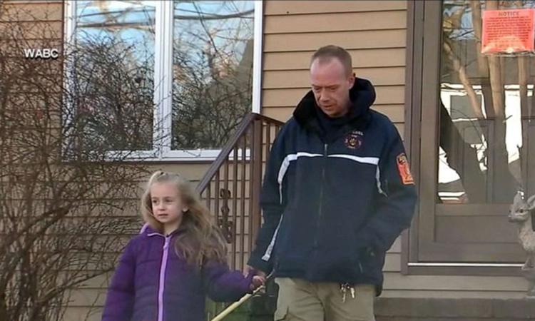 Bé gái Madalyn và bố bên ngoài ngôi nhà bị cháy của họ ở bang New Jersey hôm 19/1. Ảnh: ABC.
