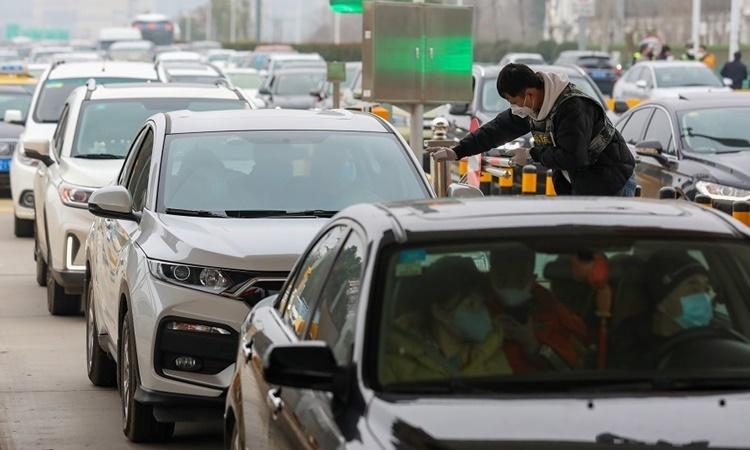 Một nhân viên y tế kiểm tra nhiệt độ của những người trên xe ôtô tại trạm soát vé trên đường cao tốc nối với sân bay quốc tế Vũ Hán Vũ Hà. Ảnh: China Daily.