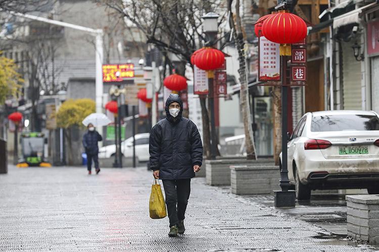 Một người đàn ông đeo khẩu trang đi qua khu dân cư ở thành phố Vũ Hán hôm qua. Ảnh: AP