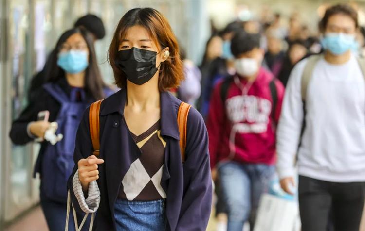 Người dân Hong Kong đeo khẩu trang khi đi bộ trên phố. Ảnh: SCMP