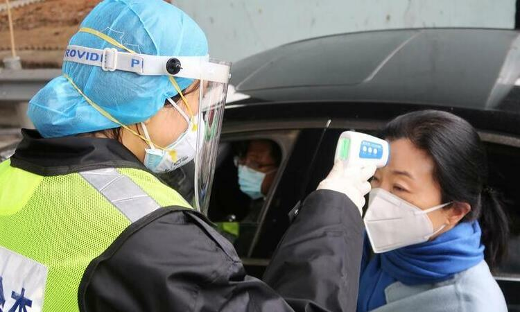 Nhân viên an ninh mặc đồ bảo hộ đo thân nhiệt hành khách tại một trạm thu phí cao tốc ở thành phố Hàm Ninh, giáp với Vũ Hán, tỉnh Hồ Bắc, Trung Quốc, hôm 24/1. Ảnh: Reuters.