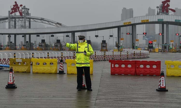 Cảnh sát làm nhiệm vụ tại một tuyến đường ở Vũ Hán, thủ phủ tỉnh Hồ Bắc, Trung Quốc ngày 25/1. Ảnh: AFP.