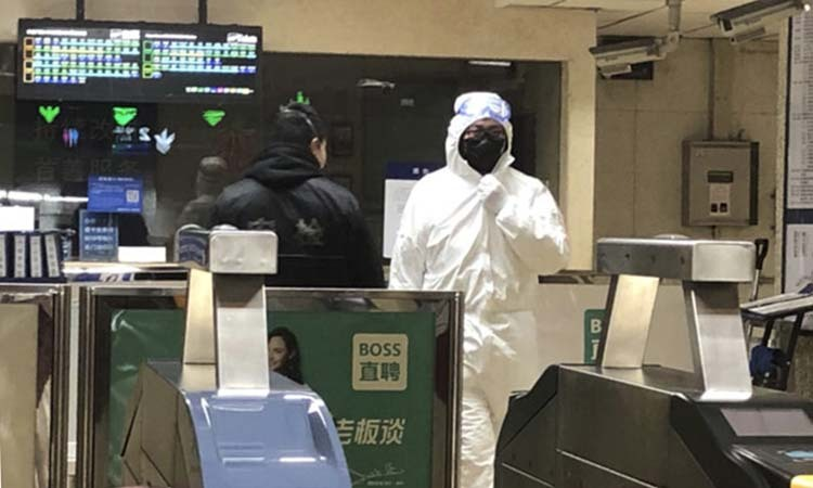 Nhân viên an ninh mặc đồ bảo hộ tại một ga tàu điện ngầm ở Bắc Kinh hôm 24/1. Ảnh: AP.