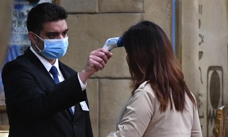Du khách bị kiểm tra thân nhiệt tại một khách sạn ở Macau, Trung Quốc, hôm 22/1. Ảnh: AFP.