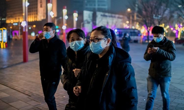Người dân đeo khẩu trang phòng chống dịch viêm phổi trên đường phố Bắc Kinh hôm 28/1. Ảnh: AFP.