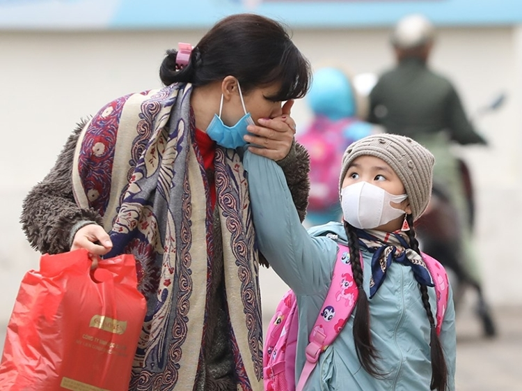 Các phụ huynh kiểm tra thân nhiệt, trang bị khăn ấm, khẩu trang cho con đi học sáng 31/1. Ảnh: Ngọc Thành