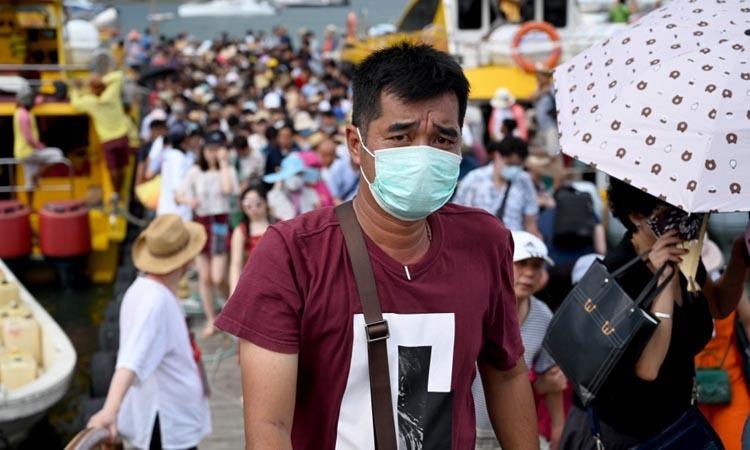 Một du khách Trung Quốc đeo khẩu trang sau khi tới thành phố Denpasar trên đảo Bali, Indonesia hôm 26/1. Ảnh: AFP.