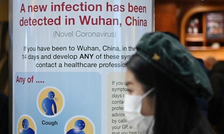 Một phụ nữ đi qua bảng thông báo dịch viêm phổi Vũ Hán tại sân bay Heathrow, London hôm 28/1. Ảnh: AFP.