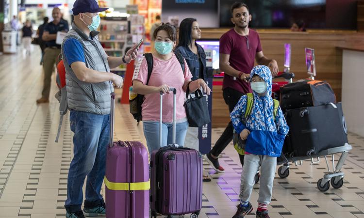 Hành khách đeo khẩu trang ở sân bay quốc tế Brisbane hôm 31/1. Ảnh: Strait Times.