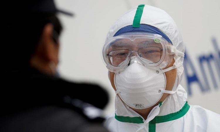 Một nhân viên bệnh viện trao đổi với cảnh sát tại một trạm kiểm soát ở tỉnh Hồ Bắc, Trung Quốc, hôm 1/2. Ảnh: Reuters.