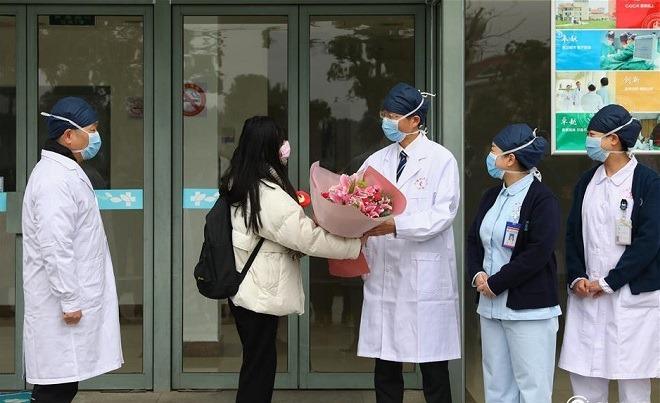 Bệnh nhân Jin (thứ 2 từ trái sang) được các bác sĩ Bệnh viện Thượng Hải tặng hoa nhân ngày xuất viện. Ảnh: Shine