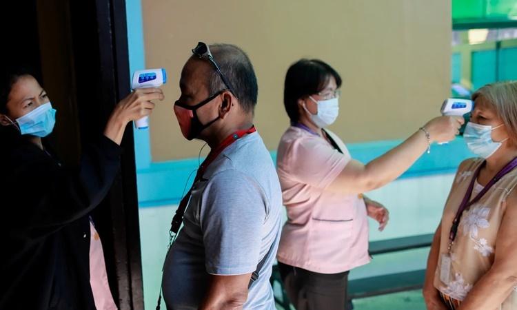 Nhân viên tại một trường học của Trung Quốc ở Philippines đeo khẩu trang để đo nhiệt độ của những người ra vào trường ngày 28/1. Ảnh: Reuters.