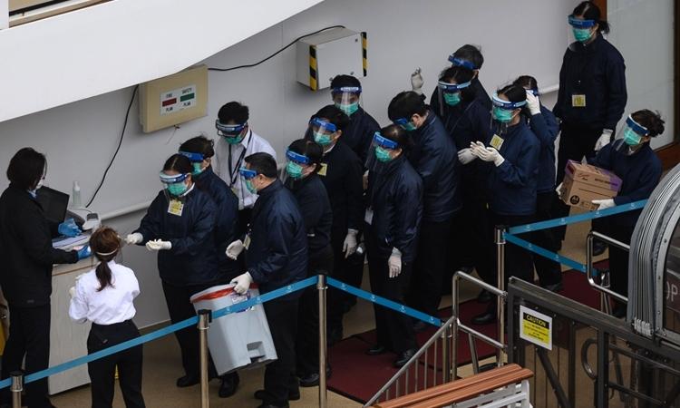 Nhân viên cơ quan y tế Hong Kong mặc đồ bảo hộ trên tàu du lịch  World Dream hôm nay. Ảnh: AFP.