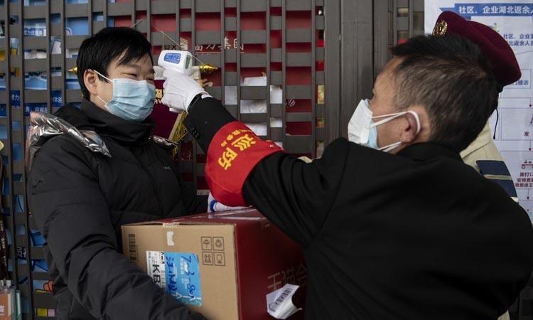 Nhân viên an ninh kiểm tra nhiệt độ người dân vào một tòa nhà ở Hàng Châu, Trung Quốc hôm 5/2. Ảnh: AFP.