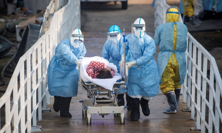 Nhân viên y tế đưa bệnh nhân nhiễm virus corona vào bệnh viện dã chiến ở Vũ Hán, tỉnh Hồ Bắc, Trung Quốc, hôm 4/2. Ảnh: Reuters.