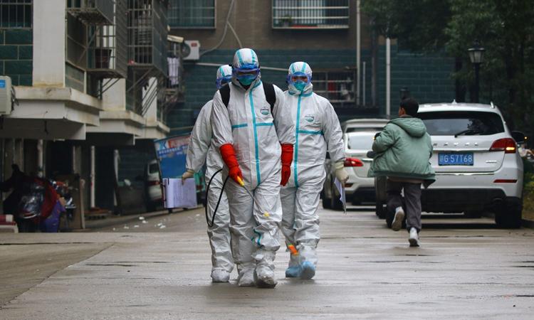 Các nhân viên trong trang phục bảo hộ khử trùng một khu dân cư ở thành phố Cửu Giang, tỉnh Giang Tây, Trung Quốc hôm 25/1. Ảnh: AFP.