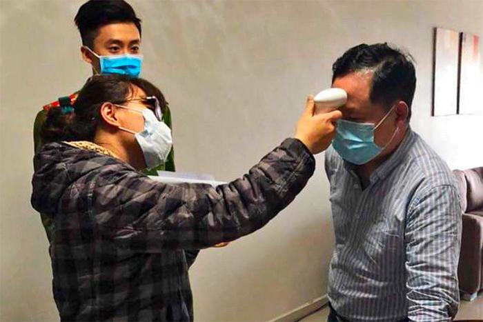Cán bộ y tế phường Mộ Lao kiểm tra thân nhiệt người bị cách ly dưới sự giám sát của công an. Ảnh: Nhân vật cung cấp