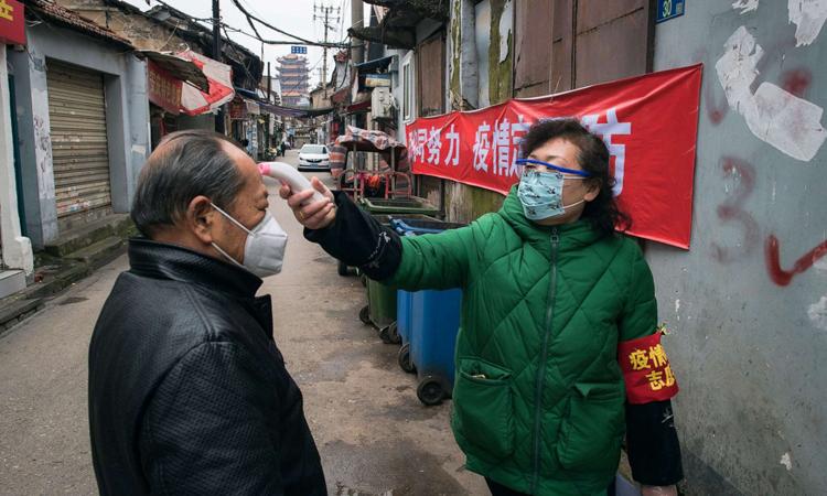 Nữ nhân viên phường đo thân nhiệt cho người đàn ông ở Hoàng Hạc Lâu, thành phố Vũ Hán hôm 7/2. Ảnh: Xinhuanet.