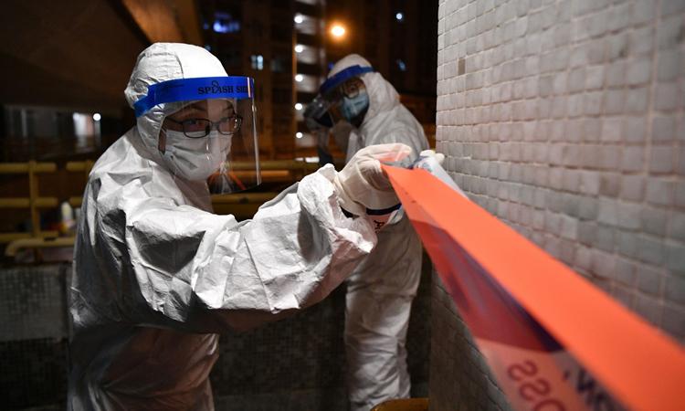 Cảnh sát mặc đồ bảo hộ phong tỏa một khu dân cư ở Hong Kong hồi cuối tháng một. Ảnh: AFP.
