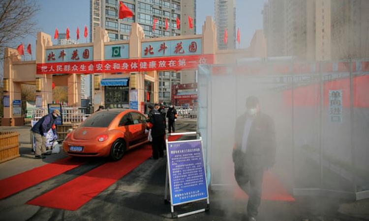 Người dân được phun khử trùng tại một khu dân cư ở Thiên Tân, Trung Quốc. Ảnh: Reuters.