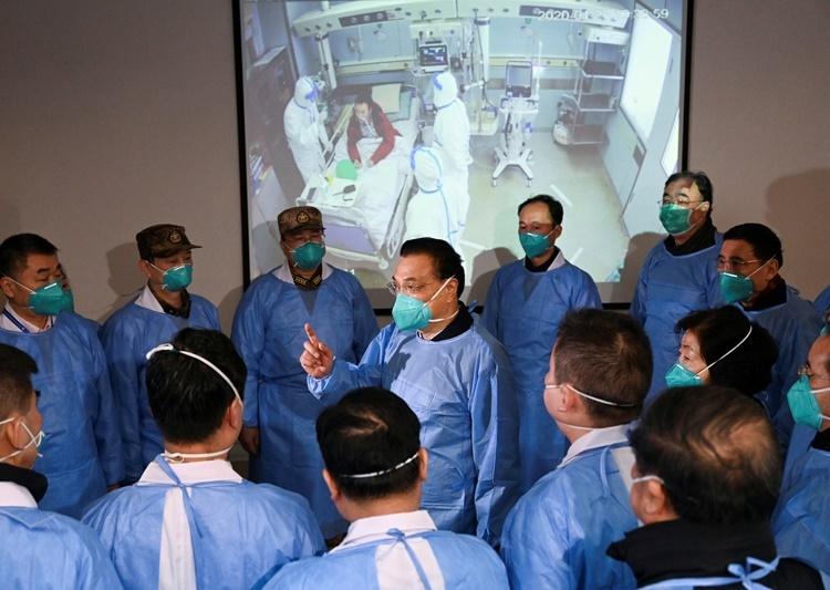 Thủ tướng Trung Quốc Lý Khắc Cường (trung tâm) nói chuyện với các nhân viên y tế tại bệnh viện Kim Ngân Đàm ở Vũ Hán cuối tháng trước. Ảnh: Reuters.