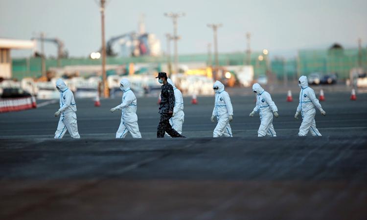 Giới chức Nhật Bản mặc đồ bảo hộ tới du thuyền Princess Diamond ở cảng Yokohama hôm qua. Ảnh: AP.