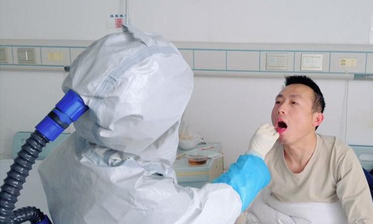 Y tá lấy dịch đờm xét nghiệm cho Shen Wufu (bên phải) tại Bệnh viện liên kết số 1, thành phố Sán Đầu, tỉnh Quảng Đông. Ảnh: WSJ.