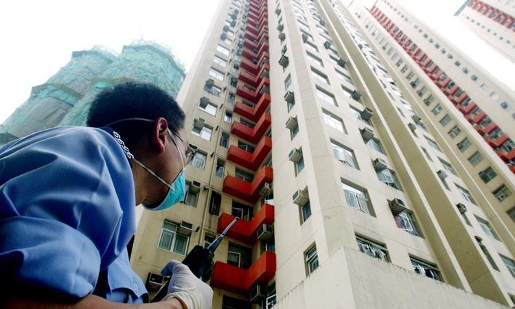 Cảnh sát canh gác lối vào một tòa nhà trong chung cư Amoy Gardens ở Hong Kong ngày 31/3/2003. Ảnh: Reuters.