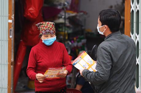 Cán bộ xã Sơn Lôi (Bình Xuyên, Vĩnh Phúc) phát tờ rơi phòng chống viêm đường hô hấp cấp do covid-19 cho người dân. Ảnh: Tất Định