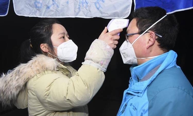 Hai người kiểm tra thân nhiệt tại Trùng Khánh ngày 30/1. Ảnh: Reuters.