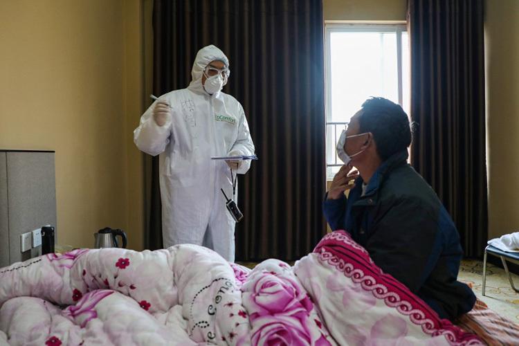 Bác sĩ (trái) trò chuyện với một nam bệnh nhân trong khu cách ly ở Vũ Hán hôm 3/2. Ảnh: AFP.