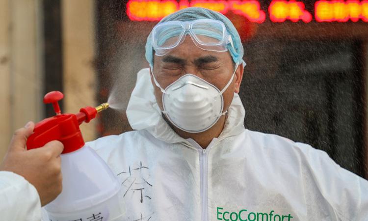 Một bác sĩ ở Vũ Hán được đồng nghiệp xịt dung dịch khử trùng hôm 3/2. Ảnh: AFP.