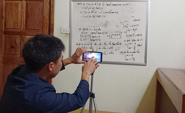 Thầy Khai tự chỉnh máy để ghi hình tại góc học tập ở nhà riêng. Ảnh: Nguyễn Khai.