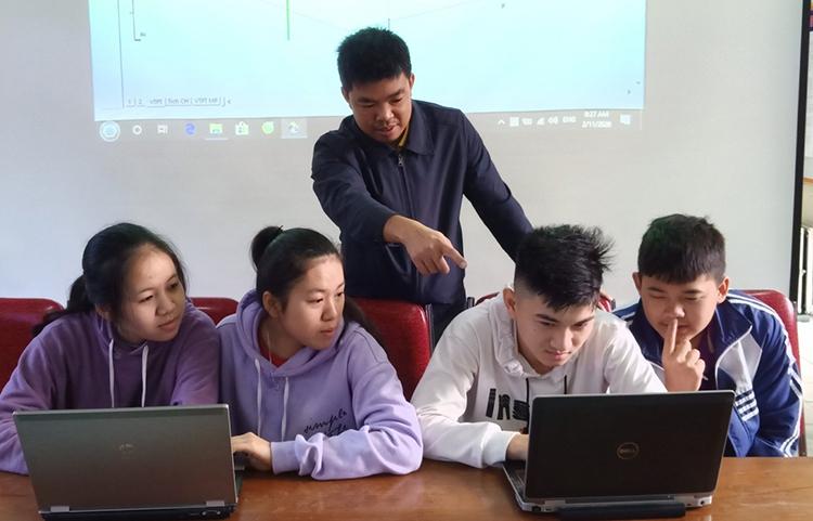 Thầy Khai (đứng hàng sau) hướng dẫn một nhóm học sinh học trực tuyến.