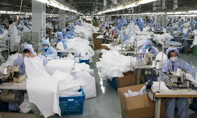 Nhân viên may quần áo bảo hộ y tế tại nhà máy ở thành phố Vô Tích, tỉnh Giang Tô hôm 8/2. Ảnh: AFP.