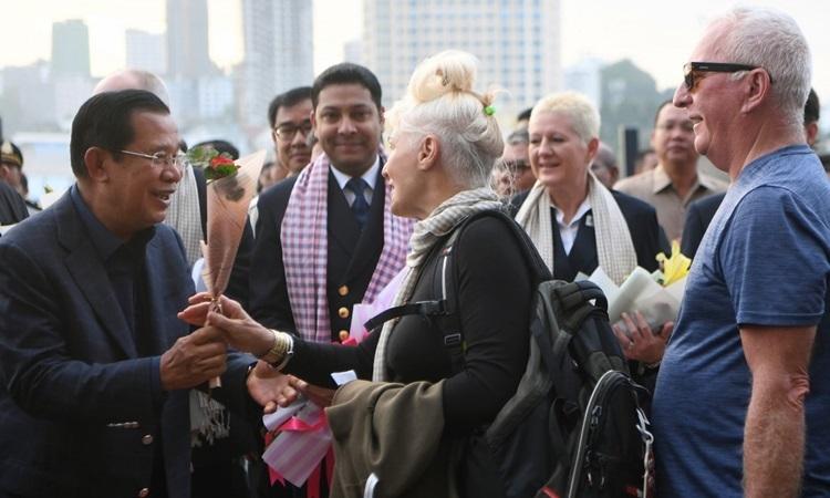 Thủ tướng Campuchia Hun Sen (trái) tặng hoa cho hành khách của du thuyền MS Westerdam hôm 14/2. Ảnh: AFP.