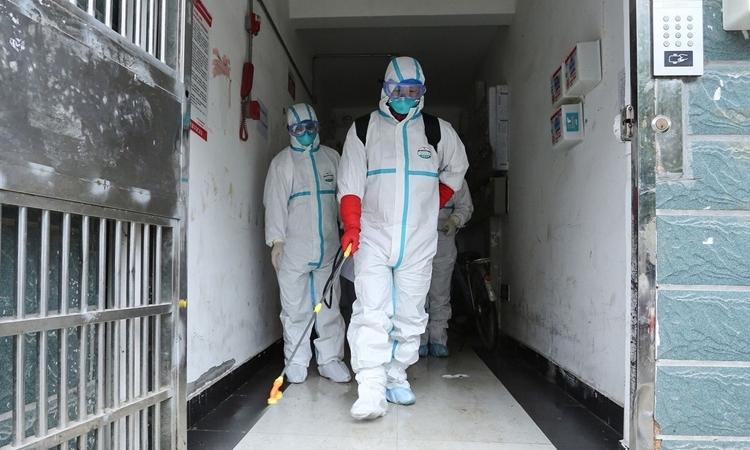 Các nhân viên vệ sinh khử trùng một tòa nhà tại Giang Tây ngày 25/1. Ảnh: AFP.
