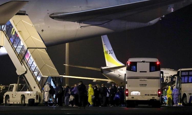 Công dân Mỹ từ tàu Diamond Princess lên máy bay về Mỹ tại sân bay Haneda ở Tokyo, Nhật Bản, rạng sáng nay. Ảnh: Reuters.