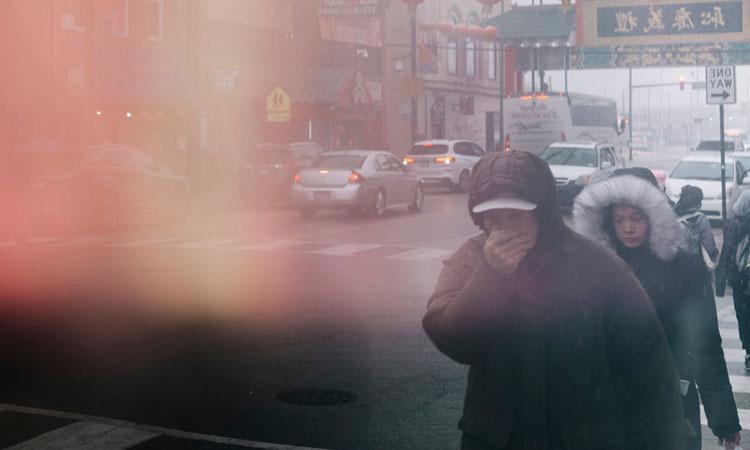 Người đàn ông lấy che miệng đi trên phố người Hoa ở thành phố Chicago, Mỹ. Ảnh: NY Times.