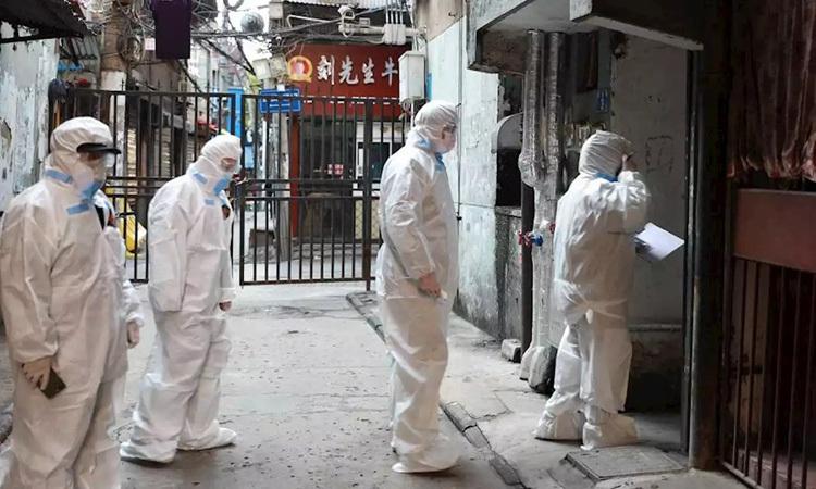 Nhân viên y tế mặc đồ bảo hộ đi kiểm tra từng ngôi nhà ở quận Giang Hán, thành phố Vũ Hán hôm 17/2. Ảnh: China Daily.
