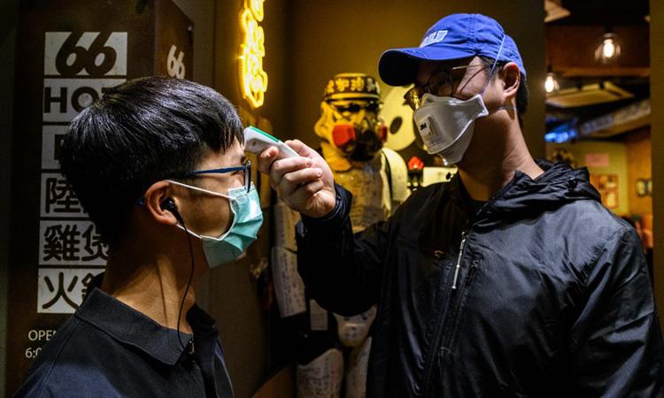 Chủ một nhà hàng ở Hong Kong đo thân nhiệt cho nhân viên hôm 13/2. Ảnh: AFP.