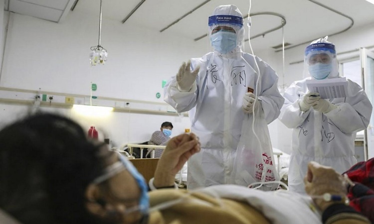Nhân viên y tế kiểm tra sức khỏe cho một bệnh nhân nhiễm nCoV tại bệnh viện Kim Ngân Đàm ở Vũ Hán. Ảnh: AFP.