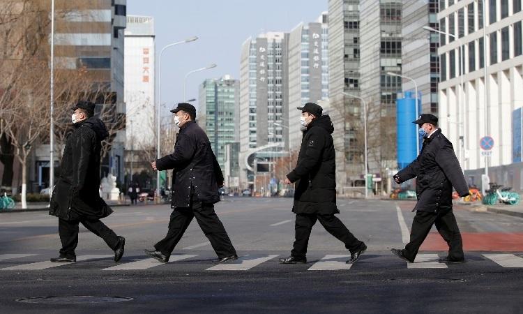 Nhân viên an ninh đi qua đường tại khu phố tài chính ở Bắc Kinh, Trung Quốc, hôm 3/2. Ảnh: Reuters.