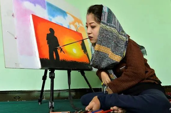 Robaba Mohammadi ngậm bút trong miệng để vẽ tranh. Ảnh: AFP.